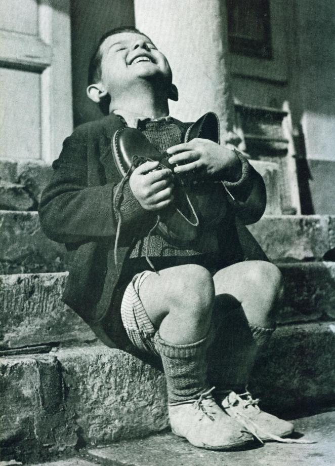 A 6 year-old orphaned boy hugs a pair of shoes given to him by the American Red Cross. Ausria, 1946 Source: Historypics