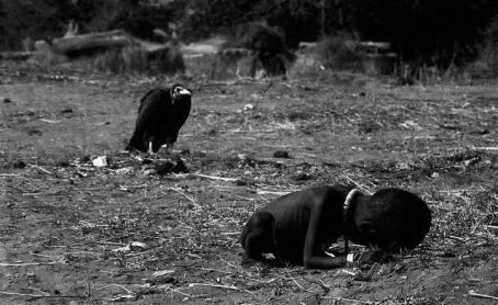 """The prize-winning image: A vulture watches a starving child in southern Sudan, March 1, 1993. Carter's winning photo shows a heart-breaking scene of a starving child collapsed on the ground, struggling to get to a food center during a famine in the Sudan in 1993. In the background, a vulture stalks the emaciated child. Carter was part of a group of four fearless photojournalists known as the ""Bang Bang Club"" who traveled throughout South Africa capturing the atrocities committed during apartheid. Haunted by the horrific images from Sudan, Carter committed suicide in 1994 soon after receiving the award."""