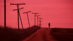 stock-footage-man-walking-on-a-country-road-red-tint